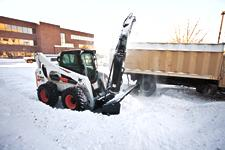 Bobcat S850 with a snowblower attachment throws snow into a truck for removal.