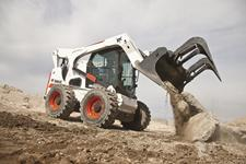 Bobcat S850 M2-Series skid-steer loader empties concrete material on a construction jobsite with a grapple attachment.