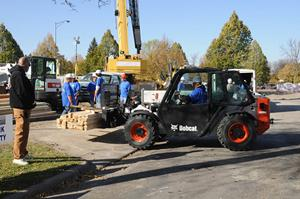 Bobcat V417 VersaHANDLER (telehandler) telescopic tool carrier lifts a pallet of pavers using the pallet fork attachment.