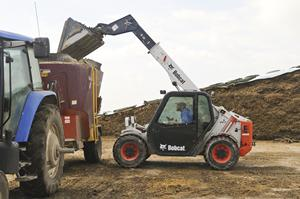 A Bobcat V417 VersaHANDLER (telehandler) telescopic tool carrier uses a bucket to lift material into a high trailer.
