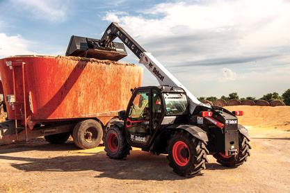 The VersaHANDLER V519 telehandler using its bucket attachment to fill a trailer.