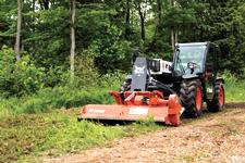 The VersaHANDLER V519 telehandler and flail cutter attachment clearing landscaping debris.