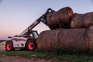 The VersaHANDLER V519 telehandler and grapple attachment lifts a round hay bale.