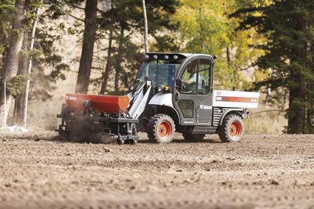 A Toolcat 5600 travels at a consistent speed while using a seeder attachment.