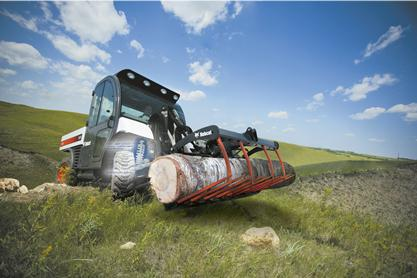 The suspension system is shown in an augmented photo of a Toolcat 5600 carrying a lot up a hill with the utility grapple attachment.