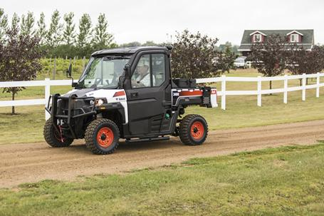 Bobcat 3400 utility vehicle with modular cab driving down a gravel road on a hobby farm.