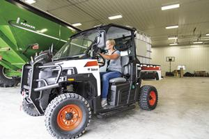 Operator drives Bobcat 3400 utility vehicle out of garage on a farm.
