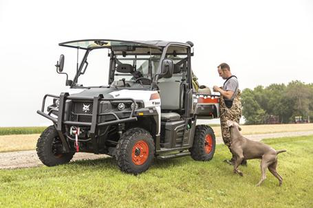 Bobcat 3600 utility vehicle with opened front windshield parked on the side of a gravel road.