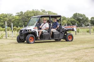 Four adults travel through a vineyard with a Bobcat 3400XL utility vehicle.