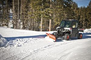 A Bobcat 3650 utility vehicle with snow blade attachment plows a path on a wooded road.