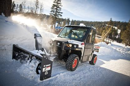 Bobcat 3650 utility vehicle with snowblower attachment clears snow on a mountain road.