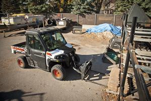 A Bobcat 3650 utiilty vehicle with pallet fork attachment lifts a pallet of pavers from a storage rack.