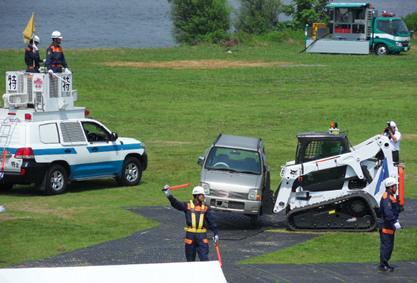 밥캣 T650 장비가 팔렛 포크로 파괴된 도로에서 손상된 차량을 치우고 있습니다.