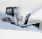 Bobcat skid-steer loader clearing snow with a snow blower attachment.