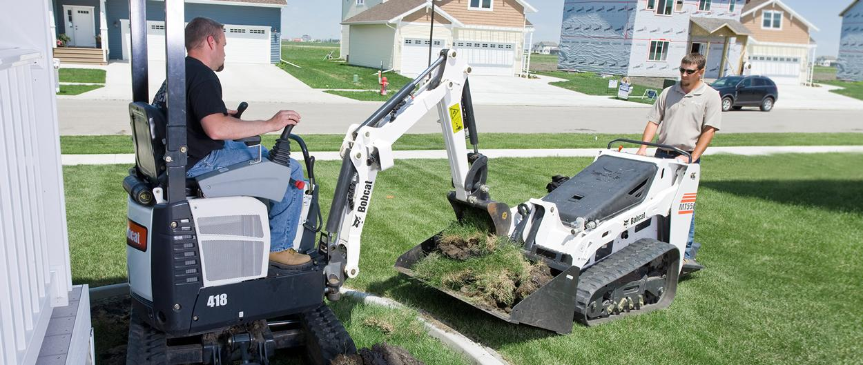 Bobcat mini track loader and compact excavator work on landscaping project.