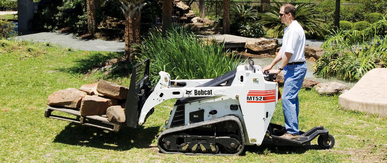 Bobcat mini track loader with pallet fork attachment hauls bricks.