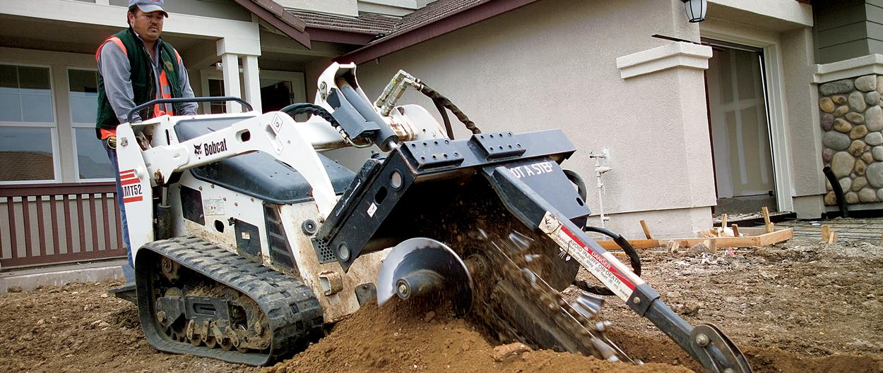 Bobcat mini track loader with trencher attachment.