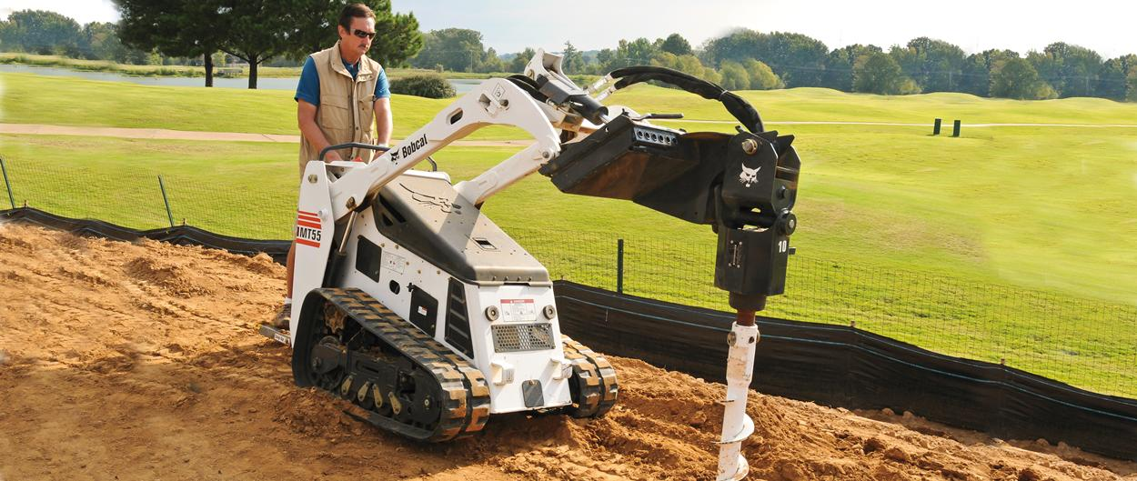 Bobcat mini track loader with auger attachment.