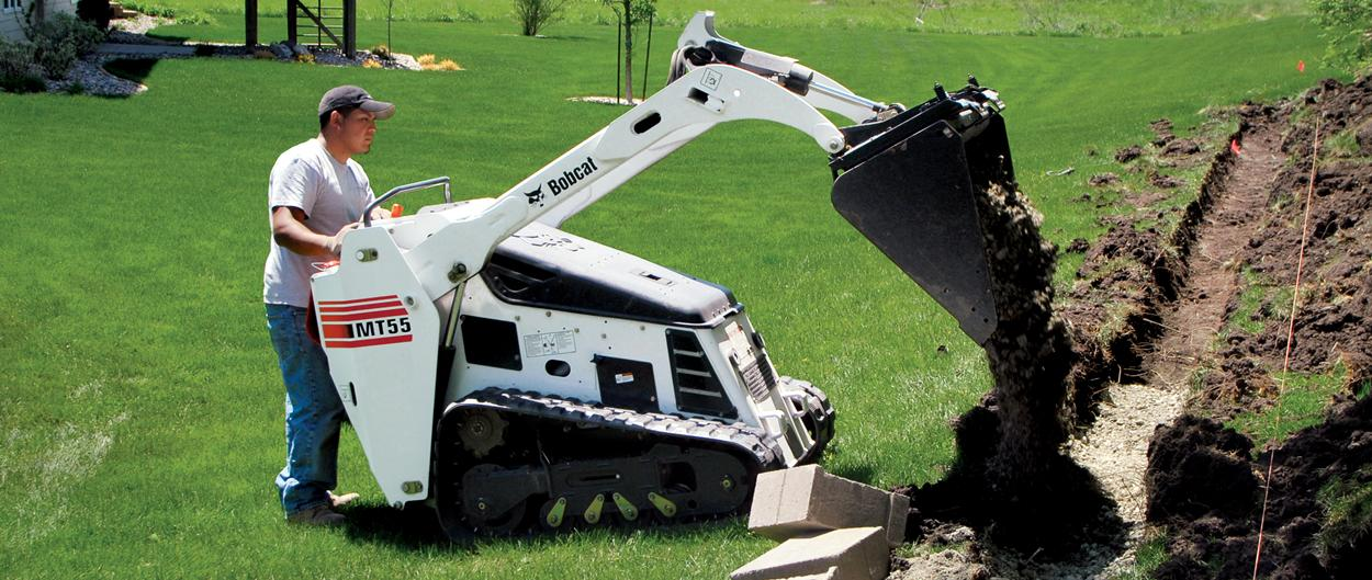 Bobcat mini track loader dumps dirt in yard.