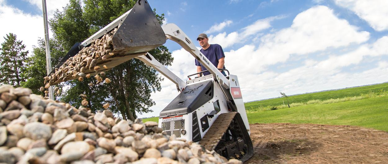 Bobcat MT85 Mini Track Loader hauls rocks with a bucket attachment.