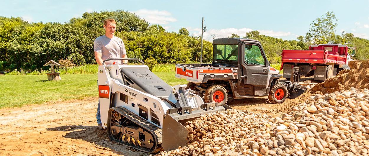 Bobcat MT55 mini track loader with bucket hauls rock.