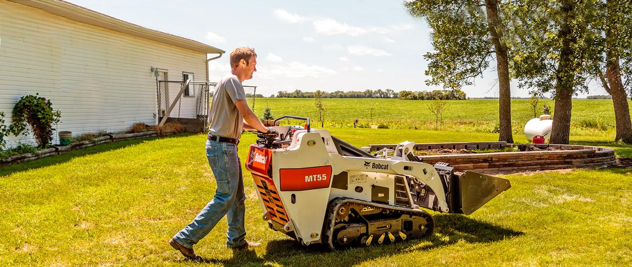 An MT55 mini track loader carries a load through a backyard while the operator walks behind.
