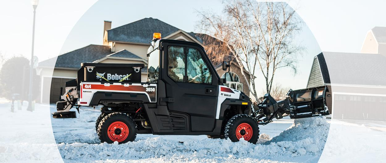 Bobcat 3650 utility vehicle with a snow V-blade and spreader attachments clearing a residential area.