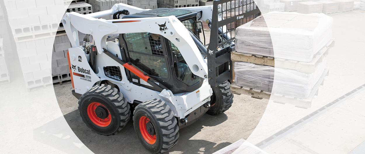 A Bobcat all-wheel steer loader with pallet forks on a construction site.