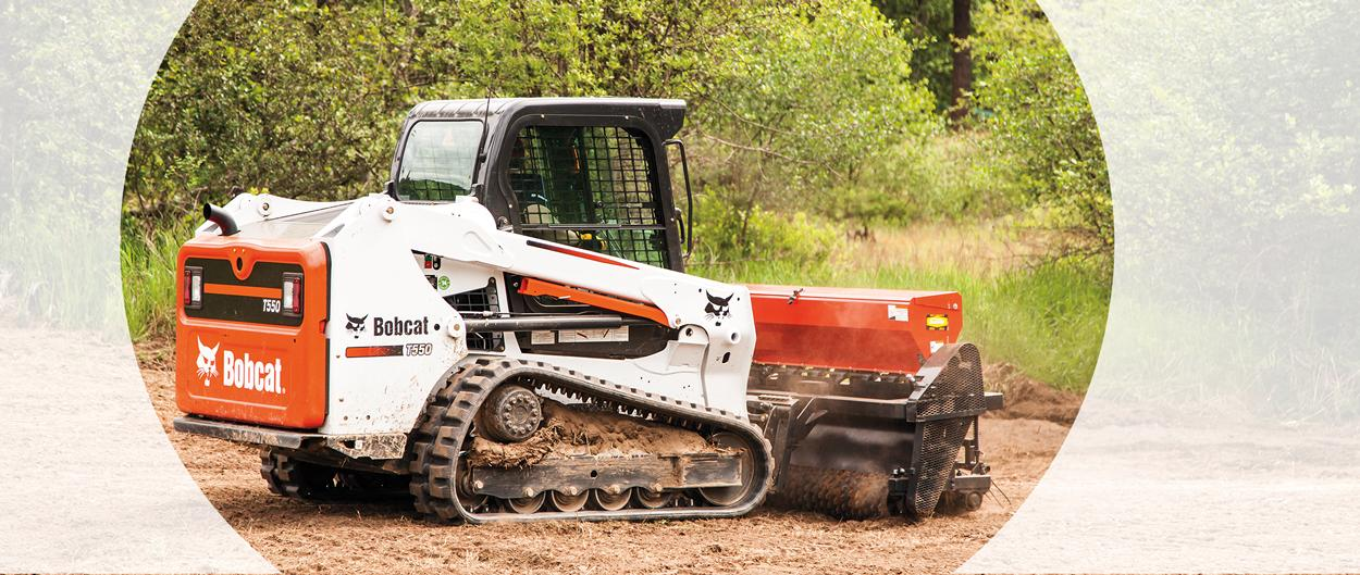 Bobcat T450 compact track loader using a bucket attachment for a landscaping job.