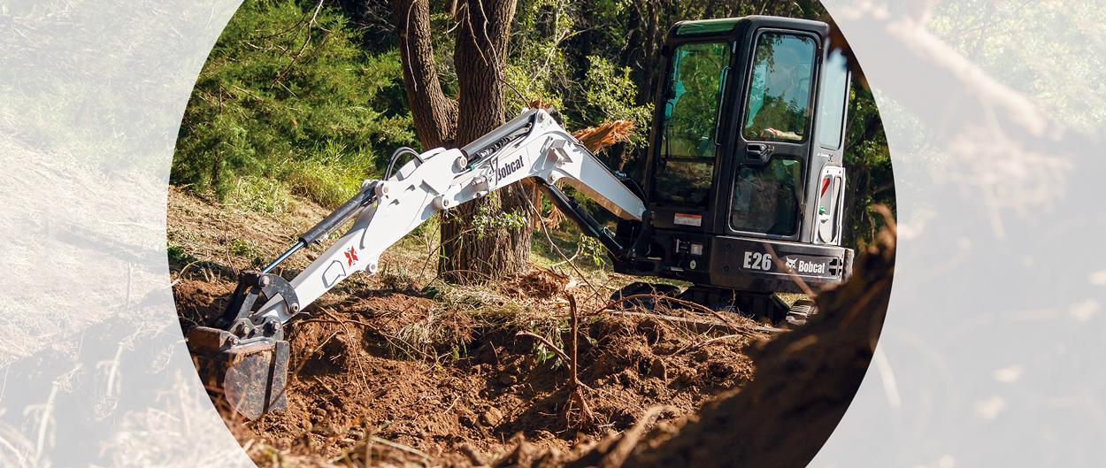 Bobcat E26 compact (mini) exzcavator with a bucket digs out a trench.