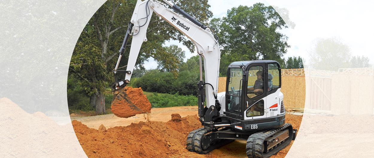 Bobcat E85 compact (mini) excavator and bucket attachment on a construction site.