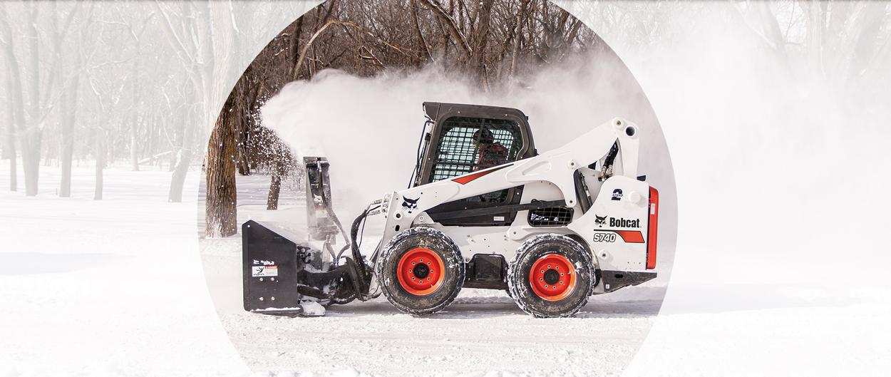 A Bobcat S740 plows snow with a snowblower attachment.