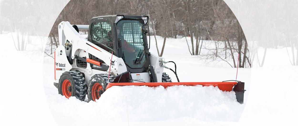 Bobcat S750 Skid-Steer Loader and snow blade attachment removing snow.