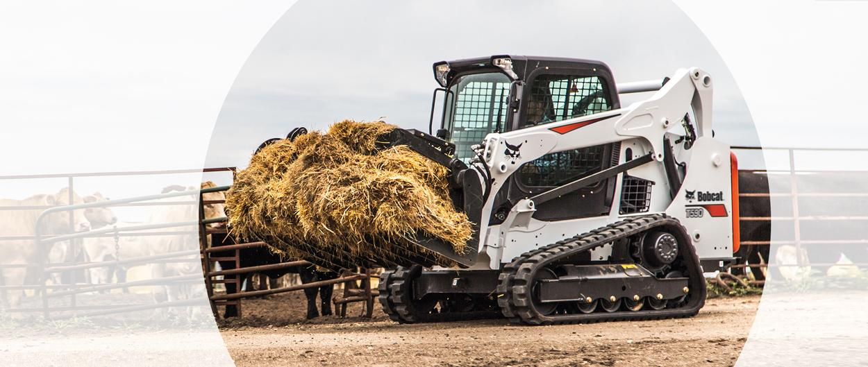 Bobcat T590 compact track loader and grapple attachment at a cattle farm.