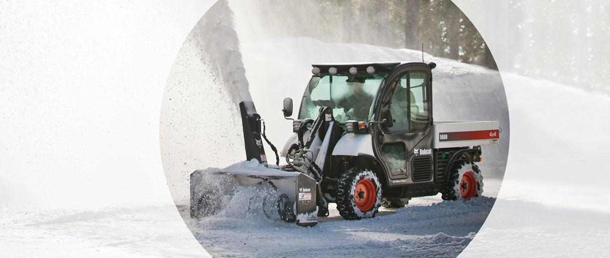 Bobcat Toolcat 5600 utility work machine and snowblower attachment clearing a path.