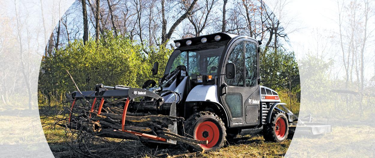 Toolcat 5610 utility work machine and utility grapple attachment are used to carry branches down a path.