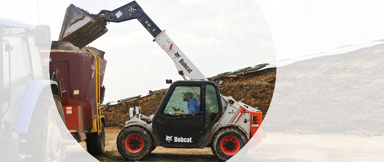 Bobcat VersaHANDLER (telehandler) telescopic tool carrier uses a bucket to lift material into a high trailer.