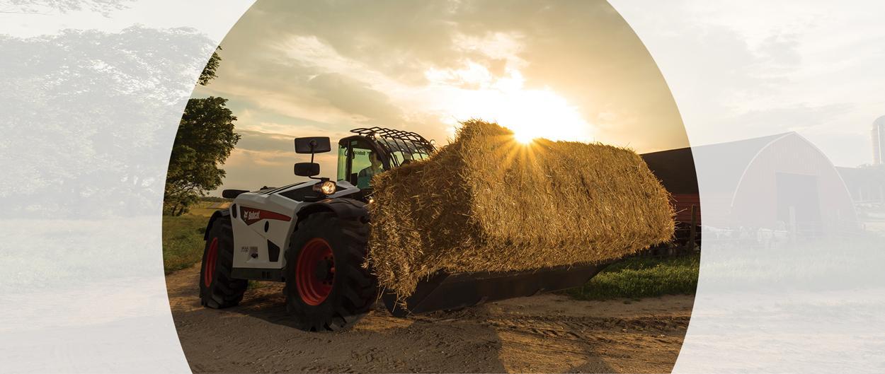 Bobcat V723 VersaHANDLER telescopic tool carrier (telehandler) with grapple attachment moving hay on a farm.