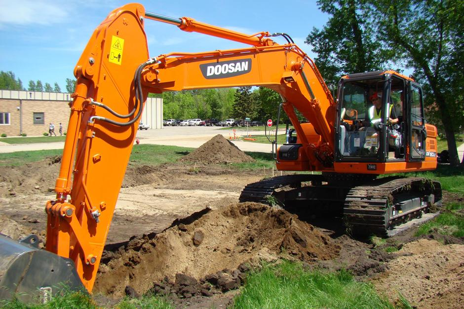 An employee uses a Doosan excavator to dig a trench during the 2014 Doosan Day of Caring.
