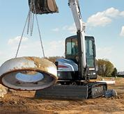 Bobcat compact excavator (mini excavator) moves heavy object.