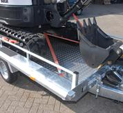 Worker uses simple machine tie downs to secure Bobcat compact excavator (mini excavator) to flatbed trailer.