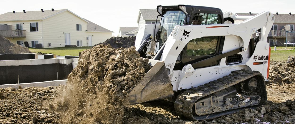 Bobcat T870 compact track loader unloads a bucket of dirt at a residential building site.
