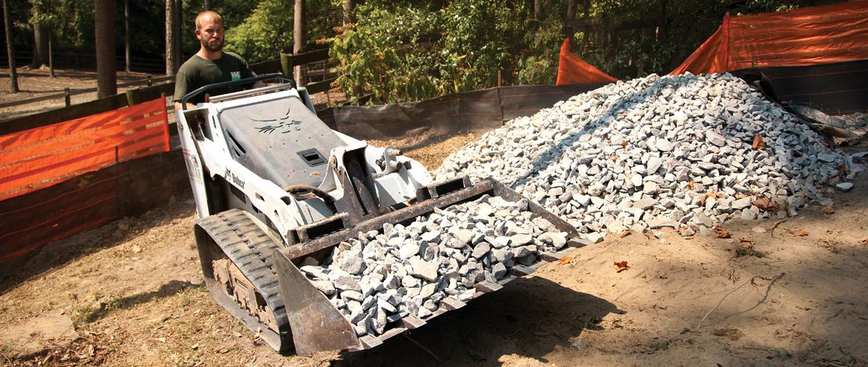 Bobcat MT55 mini track loader with bucket hauls rock.