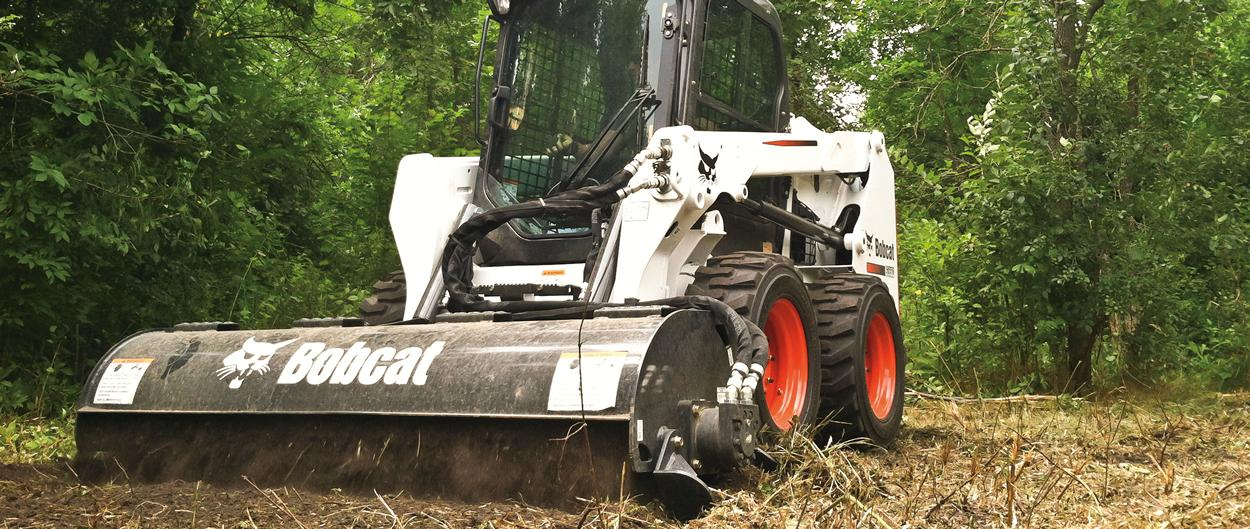 Bobcat S550 skid-steer loader with tiller attachment prepping food plot.