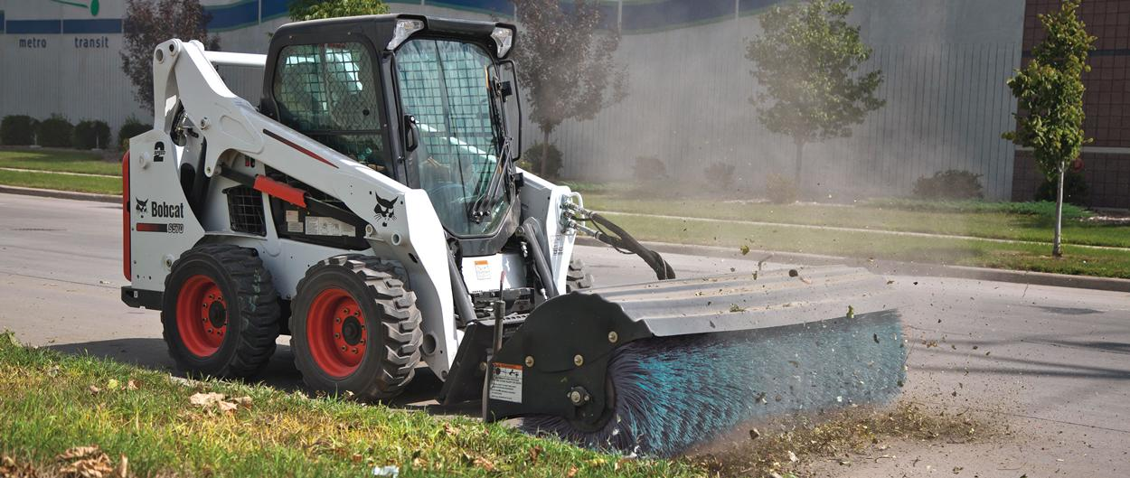 Bobcat S570 skid-steer loader with angle broom attachment.
