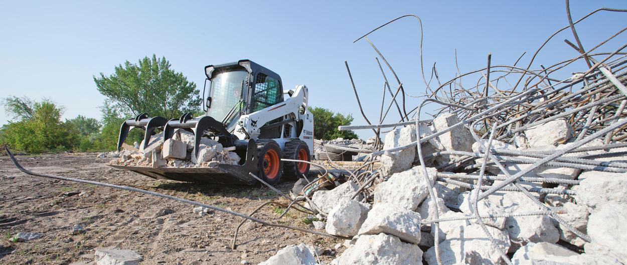 Bobcat S570 skid-steer loader dumps debris