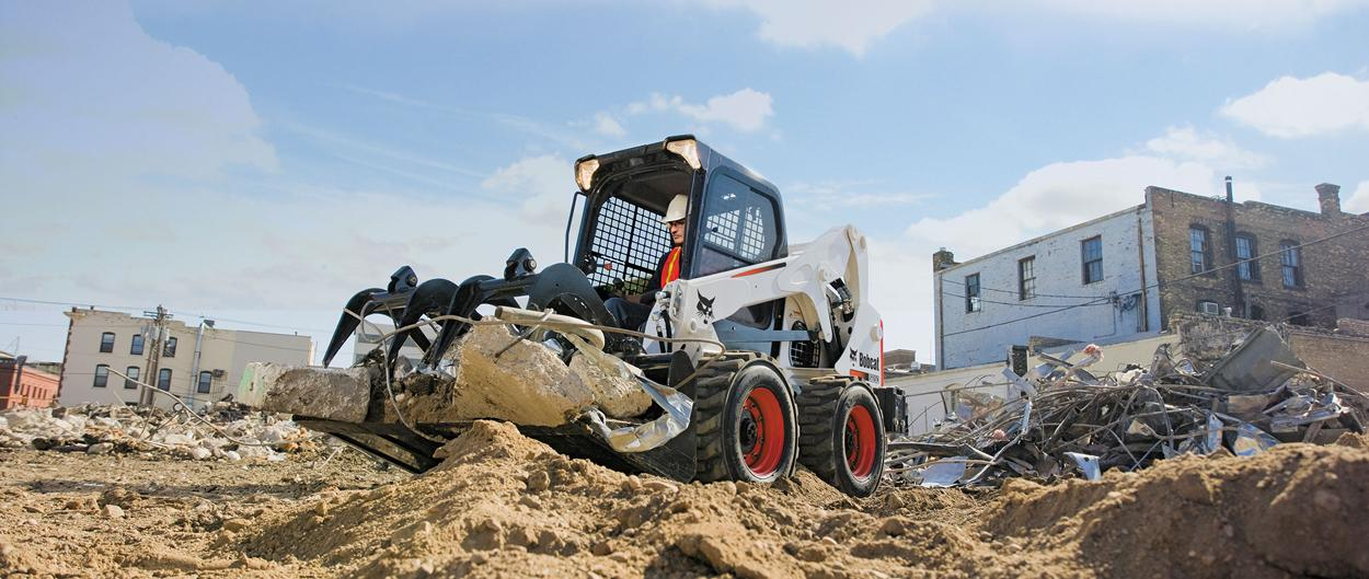 Bobcat S650 skid-steer loader with grapple attachment.