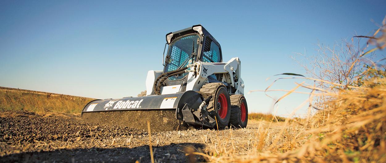 Chargeuse compacte Bobcat S630 équipée d'un cultivateur rotatif.