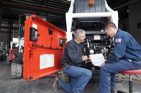 Bobcat service manager explaining service instructions to technician beside an open loader engine compartment.