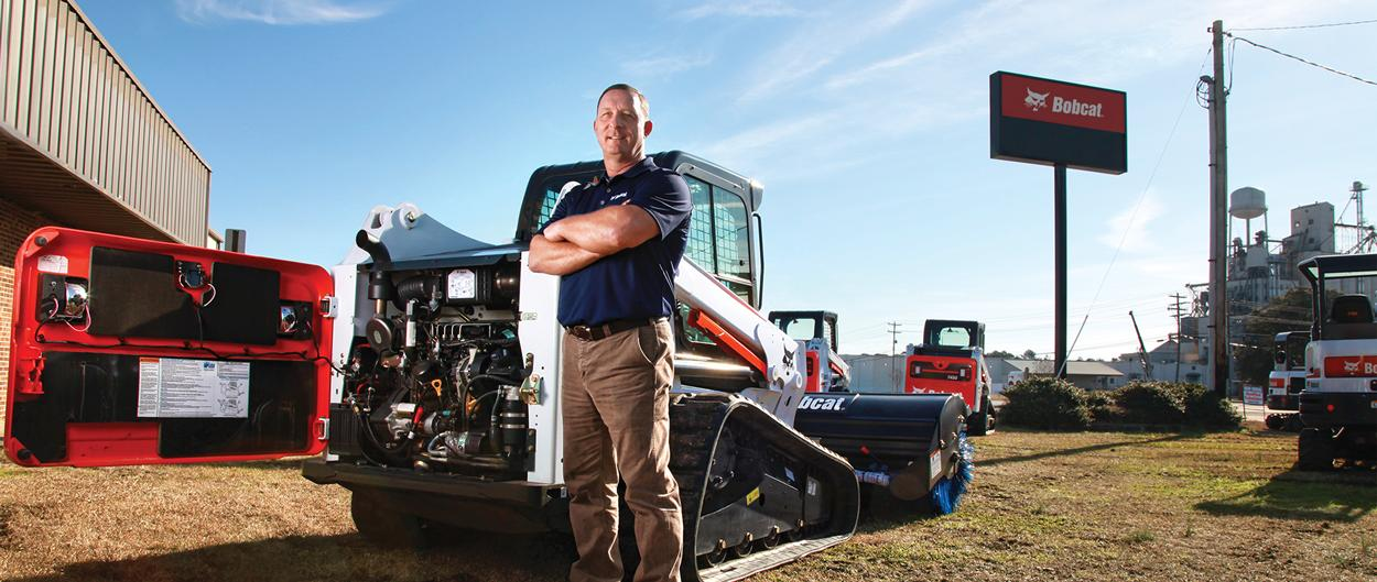 A dealer stands in front of a T630 compact track loader.